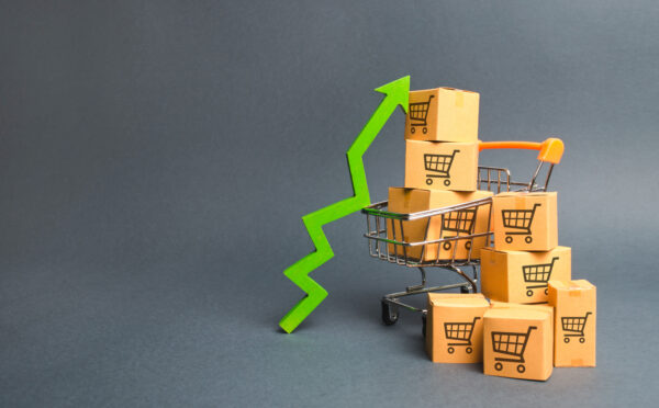 Shopping cart with cardboard boxes with a pattern of trading carts and a green up arrow. Increase the pace of sales, production of goods. Improving consumer sentiment. Strategy for increasing revenue