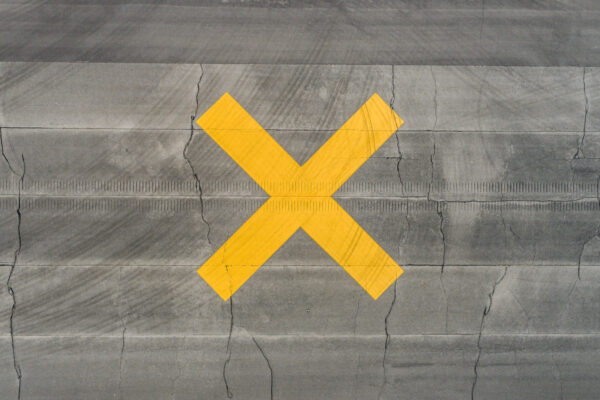 Yellow X on Wood Floor